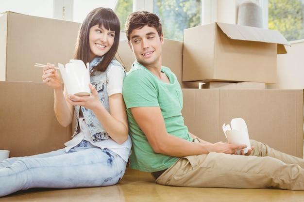 若いカップルが床に座って、彼らの新しい家で麺を食べる Premium写真