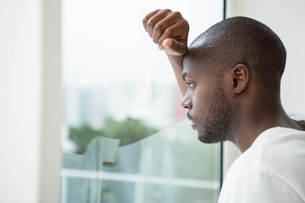 自宅の寝室の窓の外を見て思いやりのある男 Premium写真