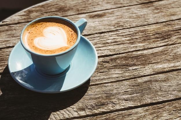 コーヒーショップで木製のテーブルの上のコーヒーアートとカプチーノのカップ Premium写真