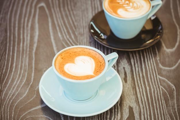 Чашка капучино с кофе искусства на деревянный стол в кафе Premium Фотографии