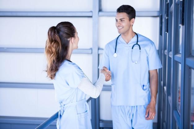 病院の廊下で握手する医師 Premium写真