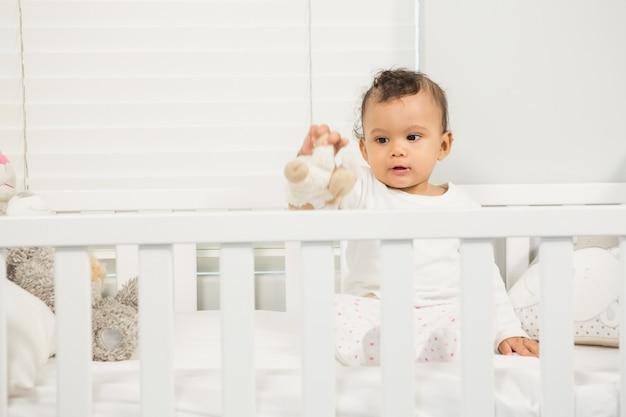 ベビーベッドで豪華な遊んでかわいい赤ちゃん Premium写真
