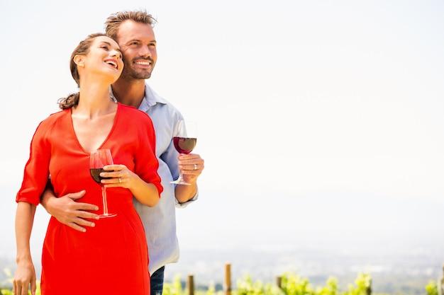 離れて見て赤ワインと笑顔のカップル Premium写真