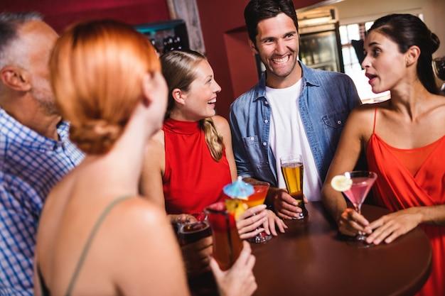 ナイトクラブのテーブルで飲み物を楽しんでいる友人 Premium写真