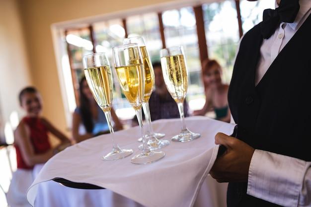 レストランでトレイにウェイトレスシャンパングラス Premium写真
