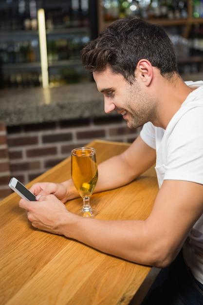 スマートフォンを使用して、ビールを持つハンサムな男 Premium写真
