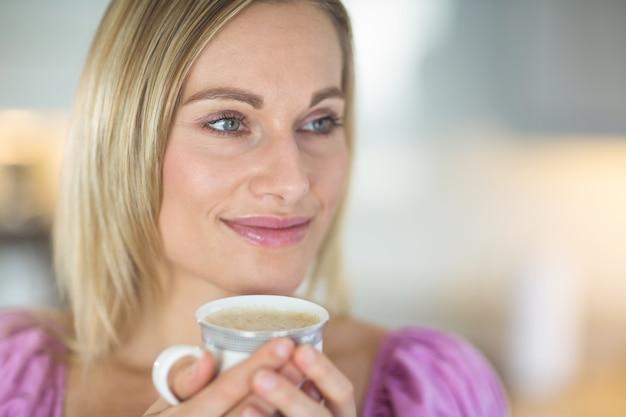 コーヒーを飲んでかなりブロンドの女性 Premium写真