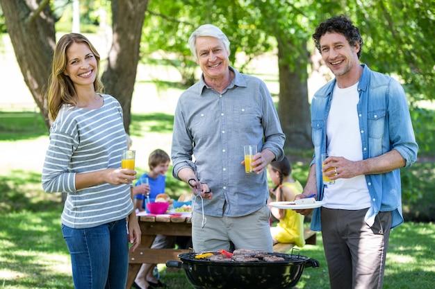 バーベキューでピクニックを持っている家族 Premium写真