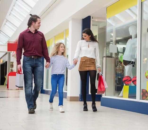 買い物袋と歩いて幸せな家族 Premium写真