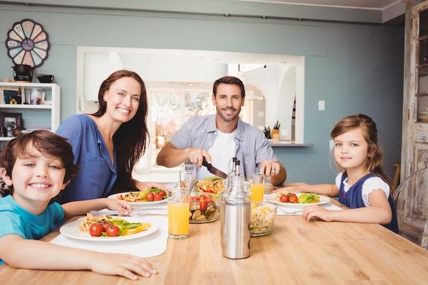 ダイニングテーブルの上に食べ物と幸せな家族の肖像画 Premium写真