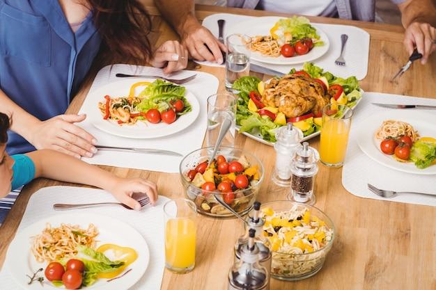 ダイニングテーブルの上に食べ物と家族の高角度のビュー Premium写真