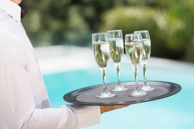 トレイにシャンパンフルートを運ぶウェイター Premium写真