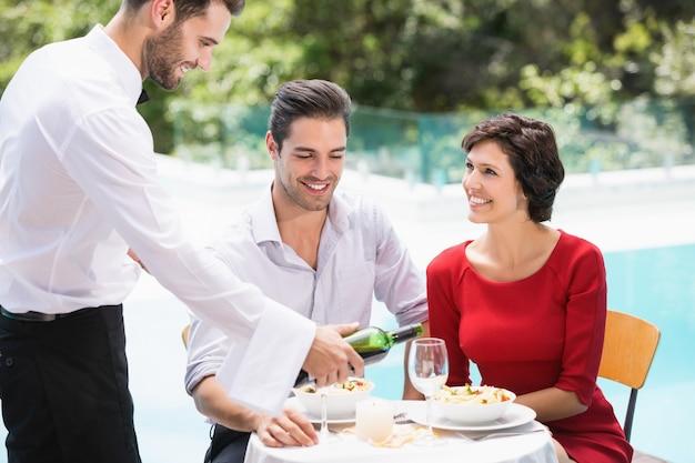 カップルに赤ワインを提供する笑顔のウェイター Premium写真