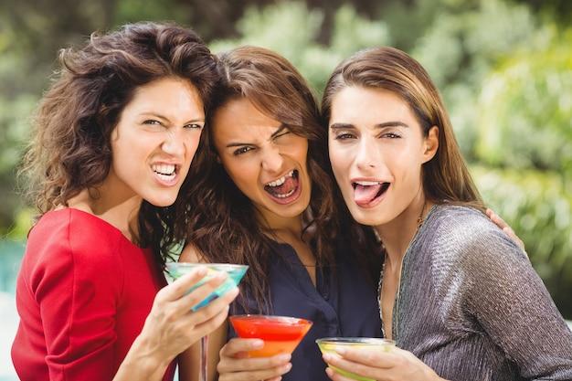 カクテルを飲みながら顔を作る女性の友人 Premium写真