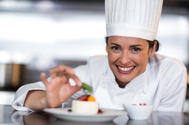食べ物を飾り幸せな女性シェフの肖像画 Premium写真