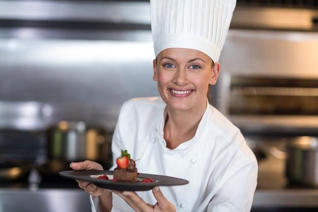 Портрет улыбается женщина шеф-повар, держа тарелку Premium Фотографии