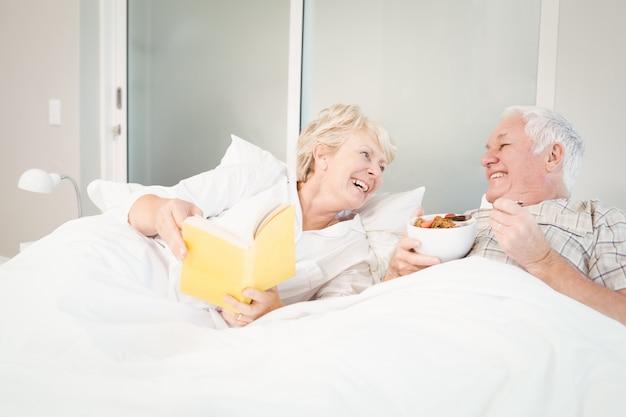 Пожилая пара читает книгу в постели Premium Фотографии