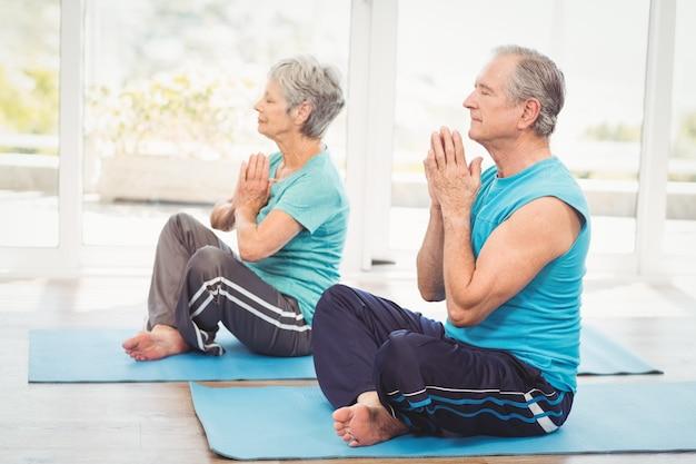 Пожилая пара выполняет йогу Premium Фотографии