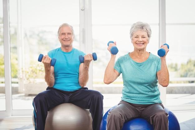 ダンベルを保持している年配のカップルを笑顔の肖像画 Premium写真