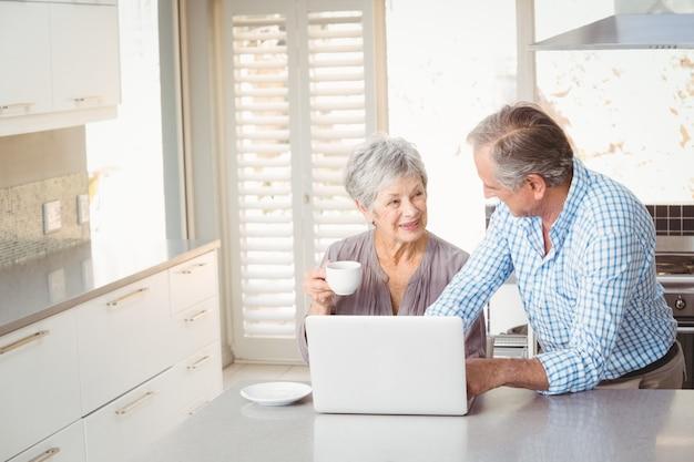 キッチンで相互作用する年配のカップル Premium写真