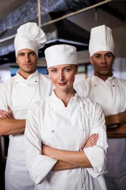 Группа поваров, стоя с руками, скрещенными на кухне Premium Фотографии