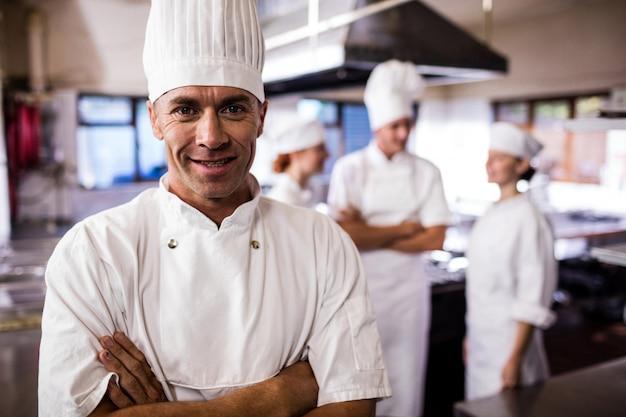 Мужской шеф-повар, стоя со скрещенными руками, в то время как коллега взаимодействует друг с другом на кухне Premium Фотографии