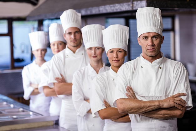 Группа поваров, стоя на кухне Premium Фотографии
