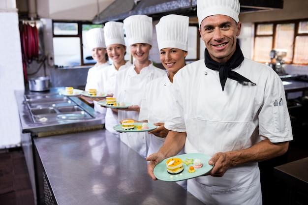 Группа поваров, держа тарелку вкусных десертов на кухне Premium Фотографии