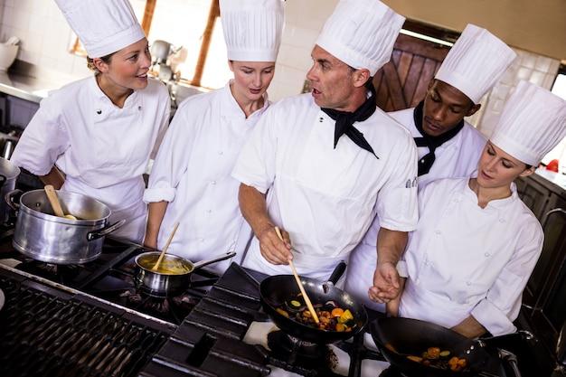 Группа поваров готовит еду на кухне Premium Фотографии