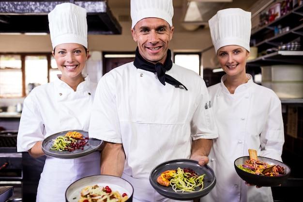 Группа поваров, держа тарелку готовой пищи на кухне Premium Фотографии