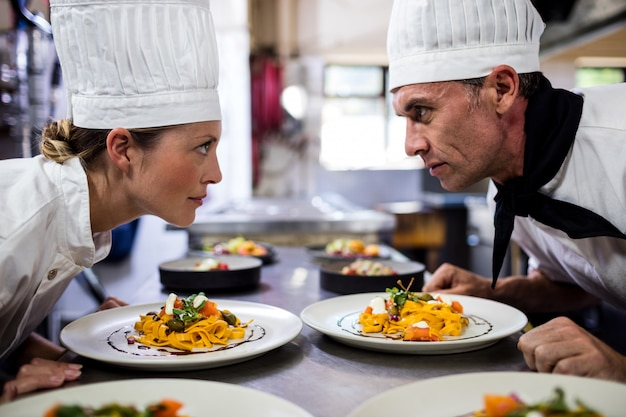 Повара мужского и женского пола, глядя друг на друга на кухне Premium Фотографии