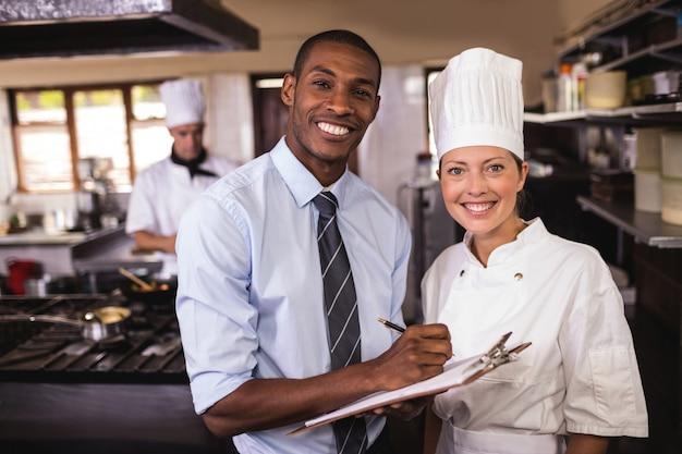 Мужской менеджер и женский шеф-повар, запись в буфер обмена на кухне Premium Фотографии
