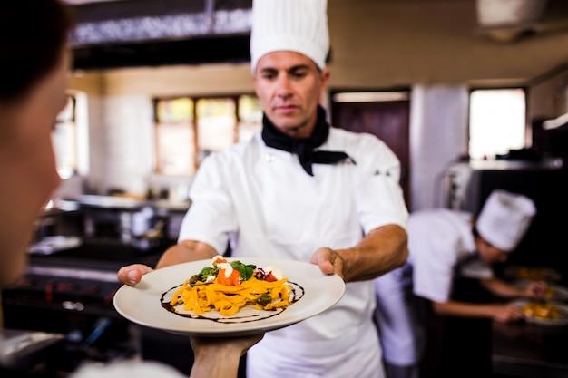 Мужской шеф-повар дает тарелку готовой пищи официантке на кухне Premium Фотографии
