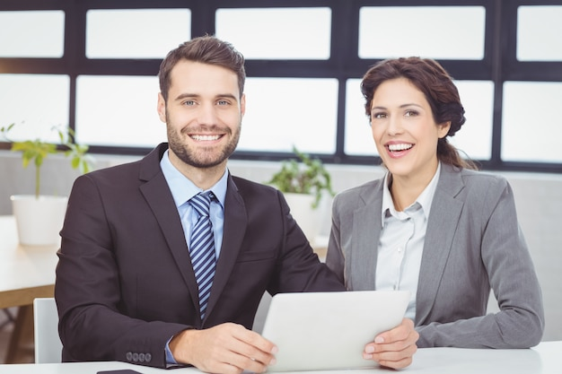 Счастливые деловые люди с цифровым планшетом в офисе Premium Фотографии