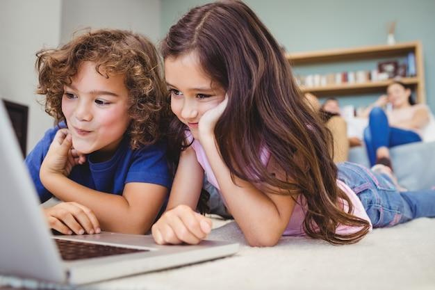 Крупным планом братьев и сестер, глядя в ноутбуке дома Premium Фотографии