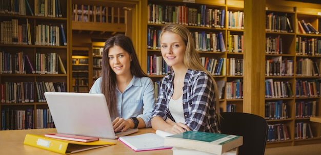 図書館でラップトップを使用して笑顔の子供達 Premium写真