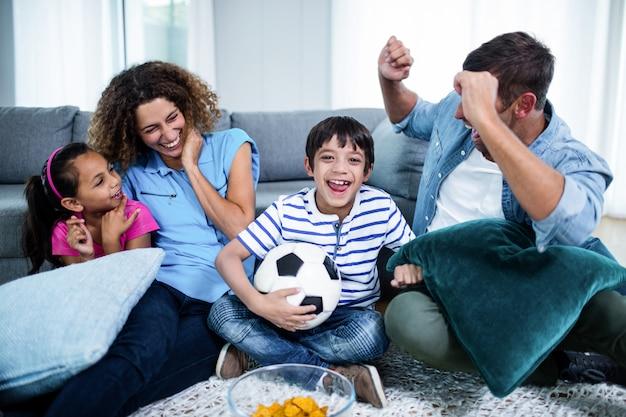 Семья смотрит матч по телевизору Premium Фотографии