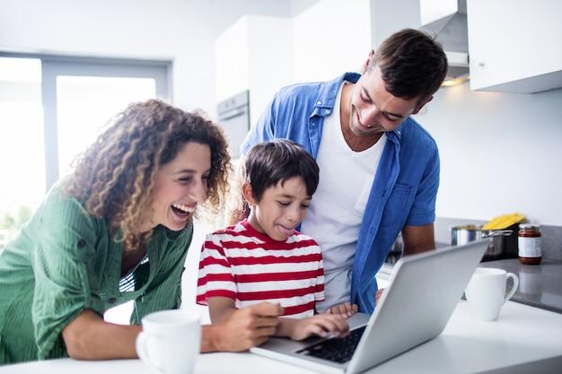 台所で息子とラップトップを使用して親 Premium写真