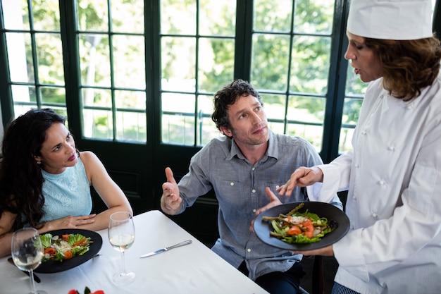 シェフに食べ物について不平を言っているカップル Premium写真