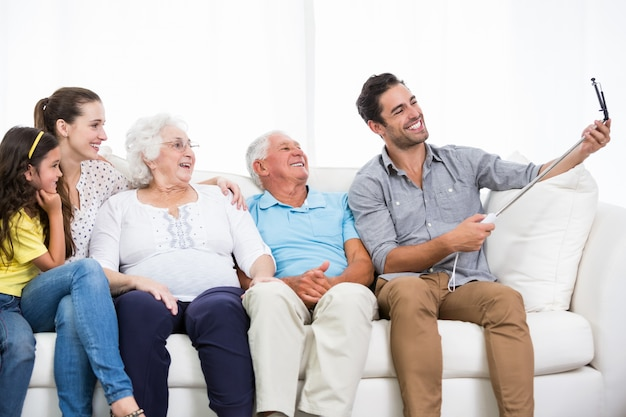 Улыбающаяся семья, принимая автопортрет, сидя на диване Premium Фотографии
