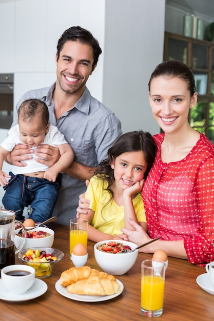 朝食のテーブルで家族の笑顔の肖像画 Premium写真