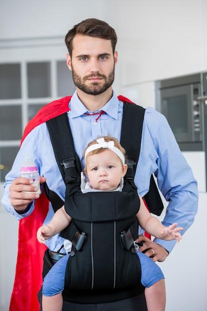 娘を運ぶスーパーヒーローの衣装の男 Premium写真