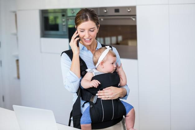 女の赤ちゃんを運んでいる間携帯電話で話している女性 Premium写真