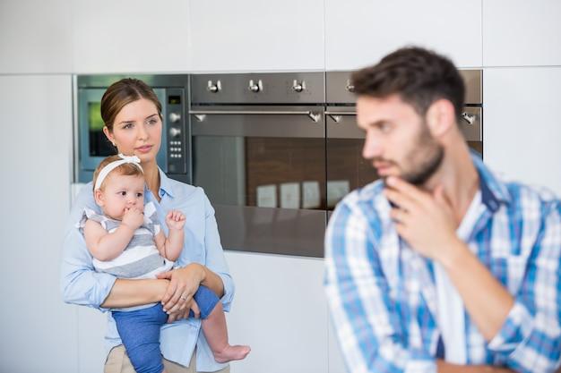 緊張した夫を見て赤ちゃんを持つ女性 Premium写真