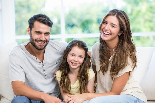 Счастливая пара сидит с дочерью на диване Premium Фотографии