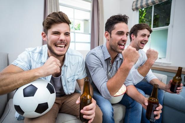 Веселые друзья-мужчины смотрят футбольный матч по телевизору Premium Фотографии