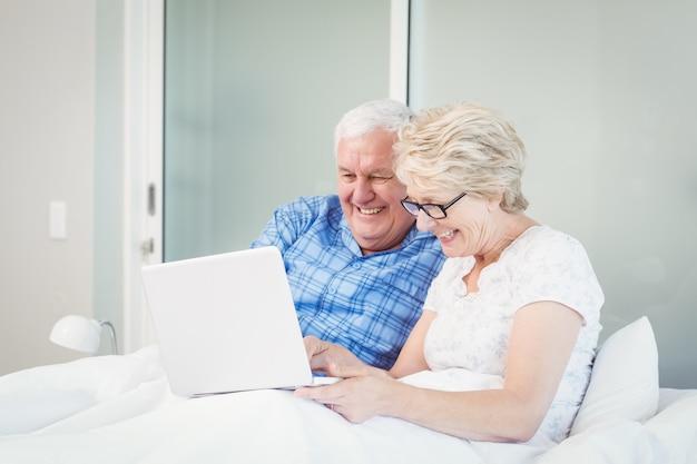 ベッドの上のラップトップを使用して幸せな先輩カップル Premium写真