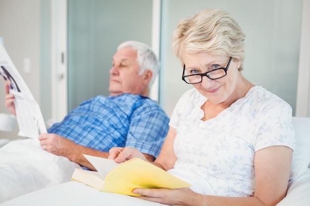 年配のカップルがベッドで読書 Premium写真
