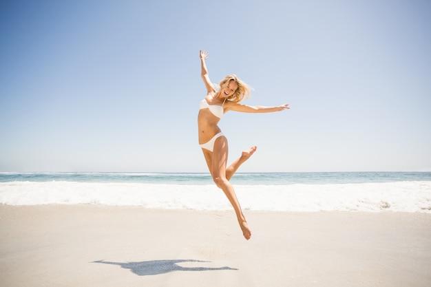 ビーチでジャンプ女性 Premium写真