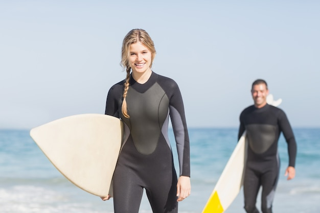 ビーチの上を歩くサーフボードとカップルの肖像画 Premium写真